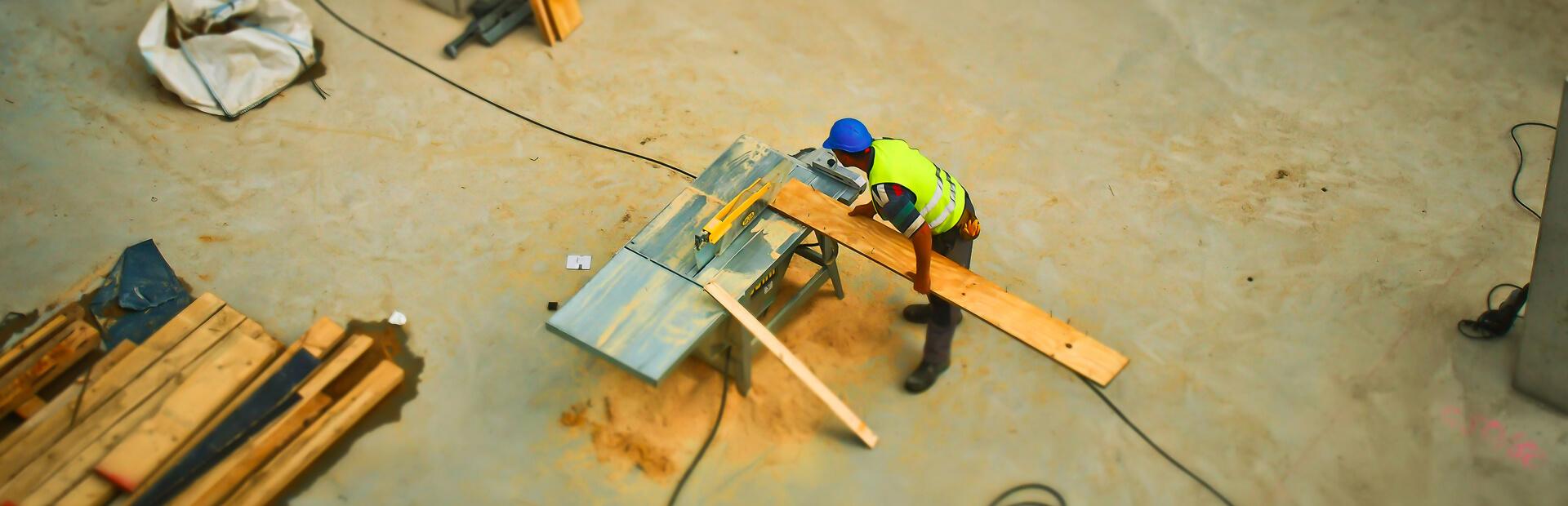 Baustellenarbeiter beim zuschneiden von Holzplatten